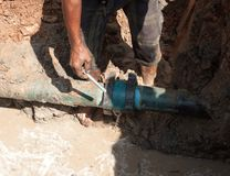 Male workers repair pipe water main broken. Tube underground water on road Stock Photo