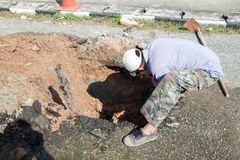 Male workers repair pipe water main broken, tube underground water on road Royalty Free Stock Images