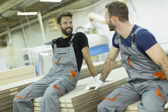 Male workers resting. Young male workers in a furniture factory taking a rest Stock Photography