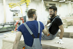 Male workers resting. Young male workers in a furniture factory taking a rest Royalty Free Stock Images
