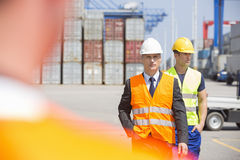 Male workers walking in shipping yard Royalty Free Stock Photo