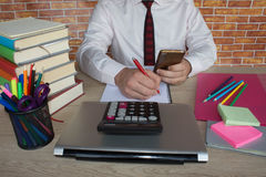 Male working with calculator, business document and laptop computer notebook. Young Businessman Calculating Finance Bills In Office Stock Image