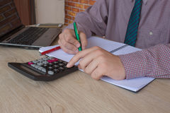 Male working with calculator, business document and laptop computer notebook. Young Businessman Calculating Finance Bills In Office Royalty Free Stock Image