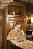 Male working on computer. Caucasian man working on laptop computer in kitchen Stock Images
