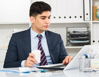Male is working at a computer and drinking coffee. In the office Royalty Free Stock Images