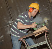Male working on electrical sanding. Picture of male working on electrical sanding and cutting timber Stock Photos