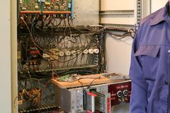 A male working electrician stands in front of an electrical panel with wires, transistors, fuses, electronics and switches royalty free stock photo