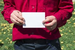Male working hands in a working shirt red burgundy color and pants dark blue holding a white sheet of paper ad rally strike. Copy space Stock Photo
