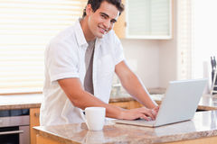 Male working on his laptop in the kitchen. Young male working on his laptop in the kitchen Royalty Free Stock Photography
