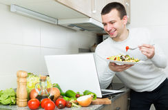 Male working and holding vegies. Satisfied young male working with laptop holding vegies in the kitchen Stock Photo