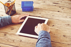 Male working at home using a tablet computer. Man working at home using a tablet computer. The male hand presses the blank screen tablet. Closeup. Top view Royalty Free Stock Images