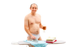 Male working in the hosue. A mature male person ironing and drinking beer in the same time Royalty Free Stock Photos