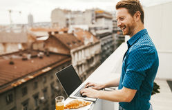 Male working on laptop on building rooftop. Male working on laptop having  beautiful view of the city Stock Image