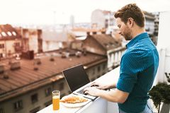 Male working on laptop on building rooftop. Male working on laptop having  beautiful view of the city Royalty Free Stock Photo
