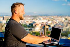 Male working on a laptop in a cafe on the roof with a beautiful panoramic view. man drinking a cocktail and working on a royalty free stock images