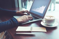 Male working with laptop and coffee cup on desk table in cafe. Shop.Business inspiration and drinking concepts ideas Royalty Free Stock Images