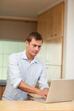 Male working on laptop in the kitchen Royalty Free Stock Images