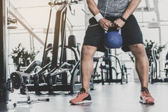 Male working out in modern gym. Close up legs of athlete exercising with kettlebell in comfortable keep-fit studio. Copy space in left side Royalty Free Stock Image