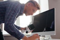 Male working with technologies. Young man working at desktop with laptop, phone and VR headset Royalty Free Stock Photography