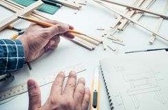 Male working on worktable with balsa wood material. Stock Photography