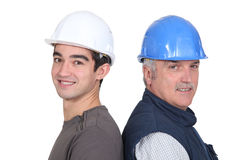 Male workmates. Standing back to back Royalty Free Stock Photography