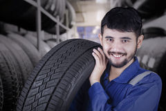 Male workshop worker carrying a tire. Young middle eastern workshop worker carrying a tire while smiling at the camera in the tire store Stock Photos
