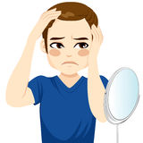 Male Worried Hair Loss. Male looking in a mirror worried about hair loss royalty free illustration