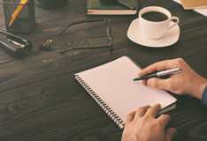 Male writes in a notebook. On a the desktop in the home office Stock Photo
