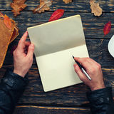 Male writes in a notebook in the park. Male writes in a blank notebook sitting at a wooden table in the park. top view Stock Photo