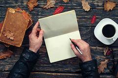 Male writes in a notebook in the park. Male writes in a notebook sitting at a wooden table in the park. top view Royalty Free Stock Photo