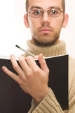 Male writing a note. Man with beard and glasses, writing something in black book. Shallow DOF, focus on book Stock Photography