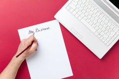 Male writing on paper near notebook. On red background Stock Photo