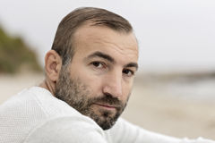 Male (brunette) with a beard in a white sweater looking at the s Royalty Free Stock Image