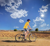 Male in yellow shirt riding a bike in Macedonia. Young male in yellow shirt riding a bike on a sunny day in Macedonia Royalty Free Stock Images
