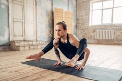 Male yoga in class, balance training. Exercise on mat in gym with grunge interior. Fit workout indoors Royalty Free Stock Photo