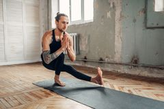 Male yoga in class, balance training. Exercise on mat in gym with grunge interior. Fit workout indoors Stock Photography