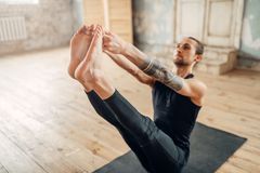 Male yoga in class, press training. Exercise on mat in gym with grunge interior. Fit workout indoors Stock Photos