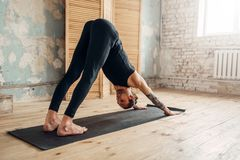 Male yoga doing stretching exercise on mat. Male yoga with tattoo on hand doing stretching exercise on mat in gym with grunge interior. Fit workout indoors Stock Photography
