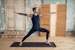 Male yoga doing stretching exercise on mat. Male yoga with tattoo on hand doing stretching exercise on mat in gym with grunge interior. Fit workout indoors Stock Image