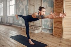 Male yoga doing stretching exercise on mat. Male yoga with tattoo on hand doing stretching exercise on mat in gym with grunge interior. Fit workout indoors Royalty Free Stock Images