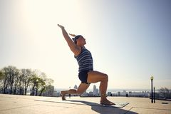 Male yoga enthusiast in warrior one pose. Montreal, Quebec, Canada Royalty Free Stock Images