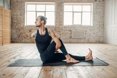 Male yoga in gym, balance exercise on mat. Fitness workout indoors. Healthy lifestyle Royalty Free Stock Photo