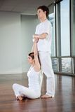 Male Yoga Instructor Assisting Woman Royalty Free Stock Photography