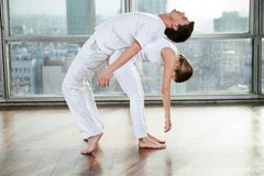 Male Yoga Instructor Assisting Woman Royalty Free Stock Photos