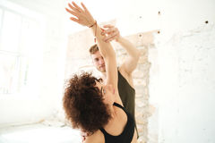 Male yoga instructor helping afro american woman. Male yoga instructor helping afro american women to do yoga stretches in a studio Stock Photography