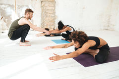 Male yoga instructor helping a woman to do yoga stretches Royalty Free Stock Photography