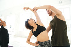 Male yoga instructor helping a woman to do yoga stretches Royalty Free Stock Image