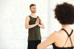 Male yoga instructor practising yoga with group of women royalty free stock image
