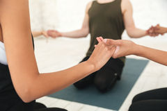 Male yoga instructor sitting in a circle. Cropped image of a male yoga instructor sitting in a circle with a group of women and holding hands meditating in a gym Stock Photo
