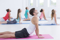 Male yoga instructor teaching class. Showing a pose to students Royalty Free Stock Image